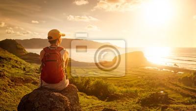 Młoda kobieta z plecak siedzi na cliff i patrząc do słońc