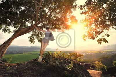 Młoda kobieta z plecak stojących na krawędzi urwiska holdin