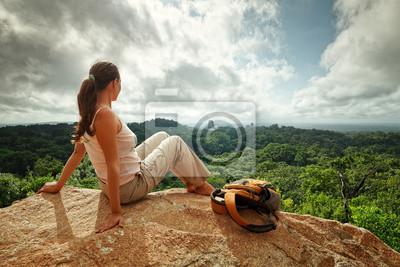 Młoda kobieta z plecakiem patrzy na ruiny Majów Tikal