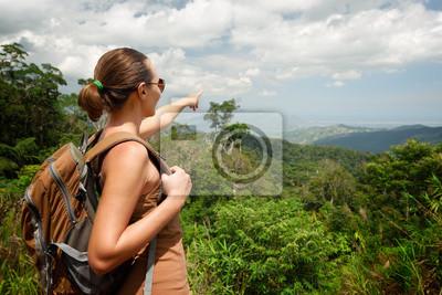 Młoda kobieta z plecakiem stoi na szczycie góry