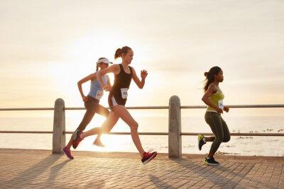 Plakat Młode kobiety poruszające się po drodze nad morzem