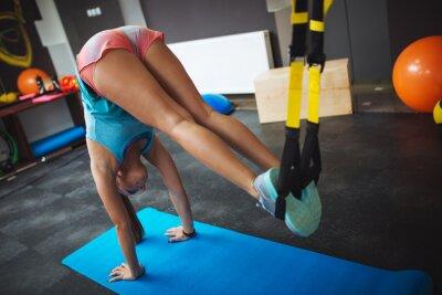 Plakat Młode samice na siłowni pracuje na jej brzucha na TRX