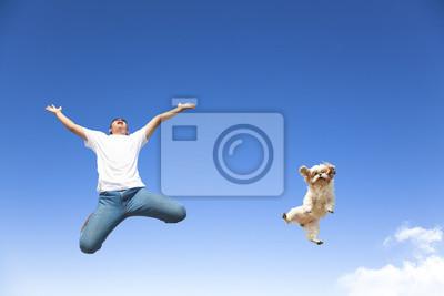 Plakat Młody człowiek i pies skacze na niebie