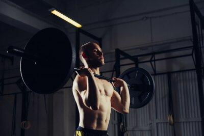 Plakat Młody człowiek podnoszenia sztangi w siłowni