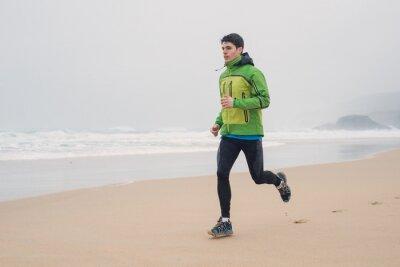 Plakat Młody mężczyzna działa na plaży w deszczowy dzień