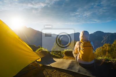 Plakat Młody podróżnik z plecakiem korzystających widoku wschodu słońca na szczycie góry, w wysokich górach
