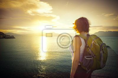 Młody turysta kobieta stoi na wybrzeżu i korzystających słońca