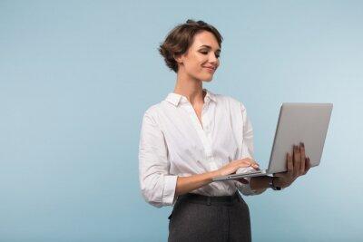 Plakat Młody uśmiechnięty bizneswoman z ciemnym krótkim włosy w białej koszula szczęśliwie pracuje na laptopie nad błękitnym tłem odizolowywającym