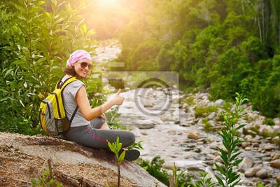 Młody wędrówki z plecakiem siedzieć i uśmiechnięta korzystających rzeka