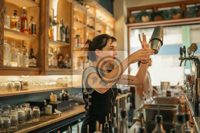 Plakat Młody żeński barman miesza koktajle za prętowym kontuarem