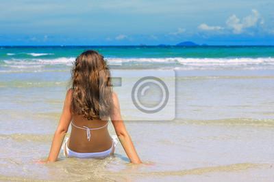 młodych szczęśliwa kobieta w białym bikini cieszy słoneczny dzień na plaży.