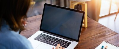 Plakat Mockup image of a woman using laptop with blank screen on wooden table