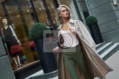 Plakat Moda. Młody stylowy kobiety odprowadzenie na miasto ulicie patrzeje na boku ciekawy
