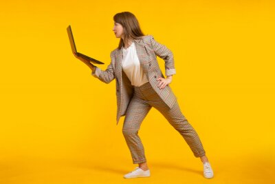 Plakat Modern businesswoman. businesswoman uses laptop. businesswoman in stylish clothes. She is posing on yellow background. Woman with open laptop in her hand. Girl in plaid suit. Stylish woman laptop