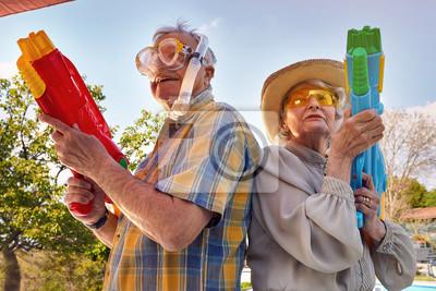 Plakat Modern Senior couple have fun playing with  water gun.