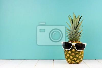 Plakat Modniś ananas z modnymi okularami przeciwsłonecznymi przeciw turkusowemu tłu. Minimalna koncepcja lato.