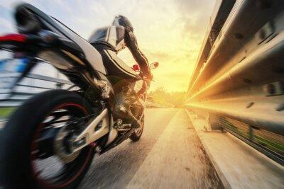Plakat Moto da strada sfreccia vicino al reling al tramonto