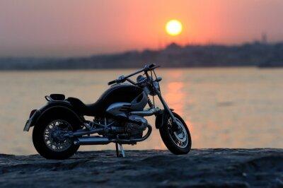 Plakat Motocykl na skałach w zachód słońca i złote godzin