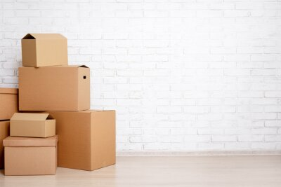 Plakat moving day concept - cardboard boxes and copy space over white brick wall