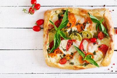 Mozzarella, pomidory, bazylia pikantne ciasto na białym tle drewnianych. Pyszne jedzenie, przystawka w stylu śródziemnomorskim. Widok z góry. Leżał płasko