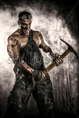 Plakat Muscular dirty coal miner with a pickaxe over dark grunge background. Mining industry. Art concept.