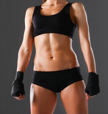 Plakat Muscular młoda kobieta stojąca na szarym tle
