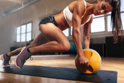 Plakat Muskularna kobieta robi intensywny trening w siłowni rdzenia