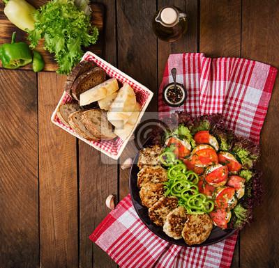 Naczynie z przekąską smażone cukinia z pomidorami i soczyste kotlety z kurczaka z cukinią. Widok z góry