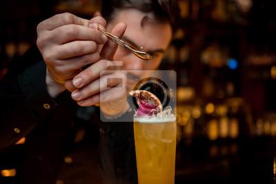 Plakat napoje alkoholowe, ludzie i koncepcja luksusu - barman ze szklanką i skórką cytryny przygotowuje koktajl w barze