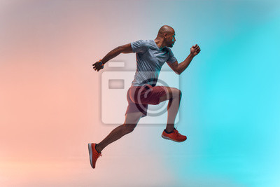 Plakat New champion. Full length of young african man in sports clothing jumping against colorful background