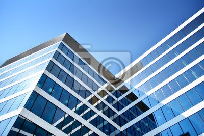 Plakat New office building in business center. Wall made of steel and glass with blue sky.