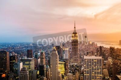 Plakat New York City skyline z miejskich wieżowców na zachód słońca.