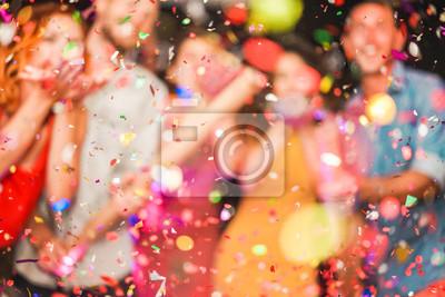 Plakat Niewyraźne osoby robiące konfetti na imprezy - Młodzi ludzie świętują w weekendową noc - Rozrywka, zabawa, Sylwester, życie nocne i koncepcja fest - Nieostre zdjęcie