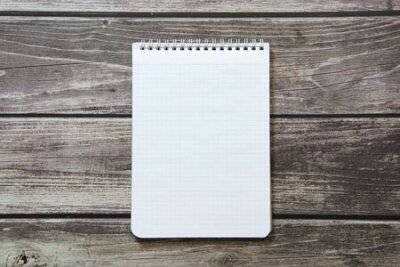 Plakat Notepad with a blank white sheet in a checker paper lies on the background of wooden boards