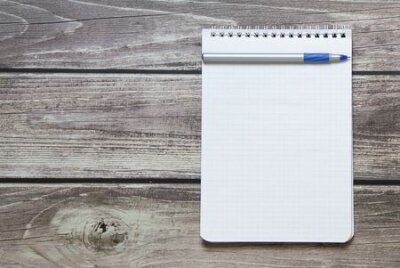 Plakat Notepad with a blank white sheet in a checker paper with ball pen lies on the background of wooden boards.