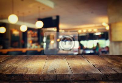 Plakat Obraz z drewnianym stole przed abstrakcyjnym tle rozmazany świateł restauracyjnych