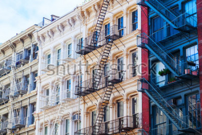 Plakat old residential buildings with fire escape stairs in Soho, New York City