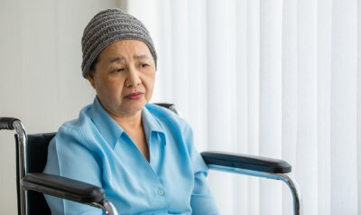 Plakat Older Asian woman patient covered the head with clothes effect from chemo treatment in cancer cure process lonely sitting on wheelchair and wait for someone to visit her
