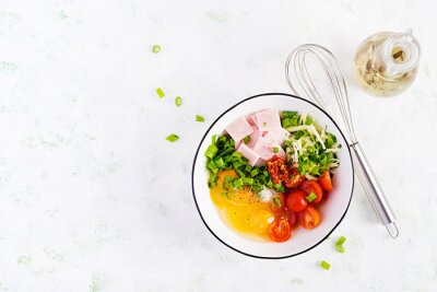 Omelette ingredients: eggs, ham, tomatoes, green herbs, milk and cheese on the light table. Top view, overhead, flat lay