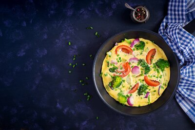 Omelette with broccoli,  tomatoes and red onions in iron skillet. Italian frittata with vegetables. Top view, overhead