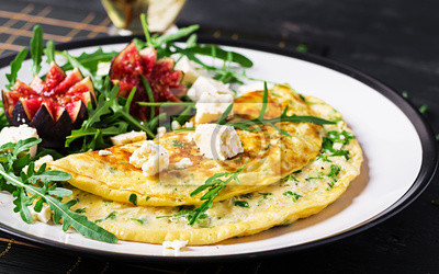Omelette with feta cheese, parsley and salad with figs, arugula on white plate. Frittata - italian omelet.