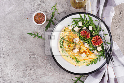 Omelette with feta cheese, parsley and salad with figs, arugula on white plate. Frittata - italian omelet. Top view. Flat lay.
