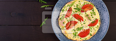Omelette with tomatoes, ham and green onion on dark table.  Frittata - italian omelet. Banner. Top view
