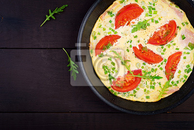 Omelette with tomatoes, ham and green onion on dark table.  Frittata - italian omelet. Top view