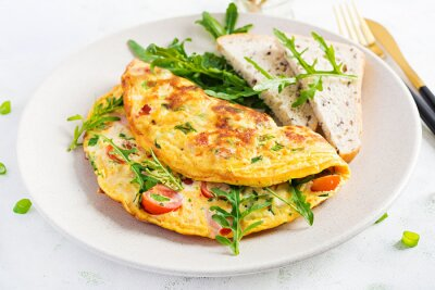 Omelette with tomatoes, ham, cheese and green herbs on plate.  Frittata - italian omelet.