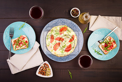 Omelette with tomatoes, ham, green onion and sandwich with strawberry on dark table.  Frittata - italian omelet. Top view