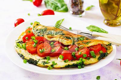 Omlet z pomidorami, szpinakiem i zieloną cebulą na bielu talerzu. Frittata - włoski omlet.