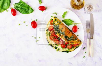 Omlet z pomidorami, szpinakiem i zieloną cebulą na bielu talerzu. Frittata - włoski omlet. Widok z góry. Płaskie leżało.