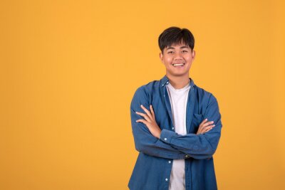Plakat On orange background With a young Asian man Happy standing.