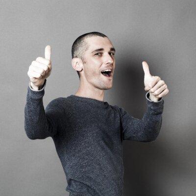Plakat Optymizm koncepcja - Excited 30s mężczyzna z krótkimi włosami i kciuki za gratulacje i powodzenia, studyjny szare tło, efekty tekstury.